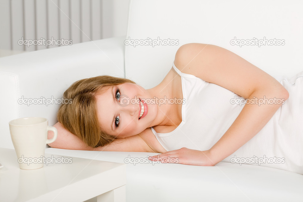 Smiling Woman Laying On Couch Stock Image