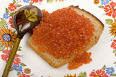 Red caviar on a piece of black bread — Stock Photo