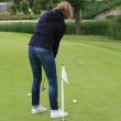 Woman practising golf on chipping green — Stock Photo