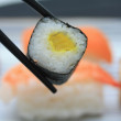 Sushi between chopsticks — Stock Photo