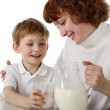 Mother pours milk to son — Stock Photo