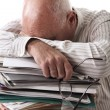 Tired senior man with papers - Stock Photo