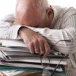 Stock Photo: Tired senior mwith papers