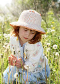 Little girl in field with dandelions — Stock Photo