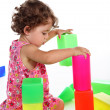 Stock Photo: Baby girl plays with toy blocks