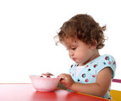 Sad little girl at table — Stock Photo