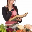 Housewife thinking with a book recipe — Stock Photo