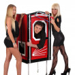 Foto Stock: Magician performance and two beauty girls in a magic box with ha