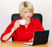 Woman with coffee-cup and laptop — Stock Photo