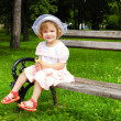 Little girl sitting on the bench in park — Stock Photo