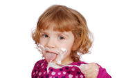 Little girl eating sweet cream — Stock Photo