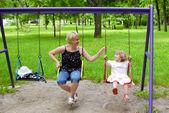 Heureuse mère et fille sur la balançoire — Photo