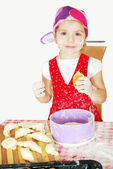 Little girl make and eat croissant — Stock Photo
