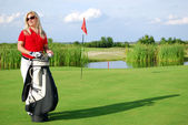 Girl with golf bag on golf course — Stock Photo