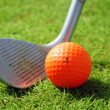 Golf-club and orange golf ball — Stock Photo