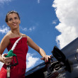 Young woman with fuel nozzle - Stock Photo