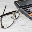 Calculator, glasses on chart newspaper — Stock Photo