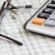 Calculator, glasses and finance - Stock Photo