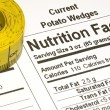 Tape Measure next to Nutrition Facts - Stock Photo