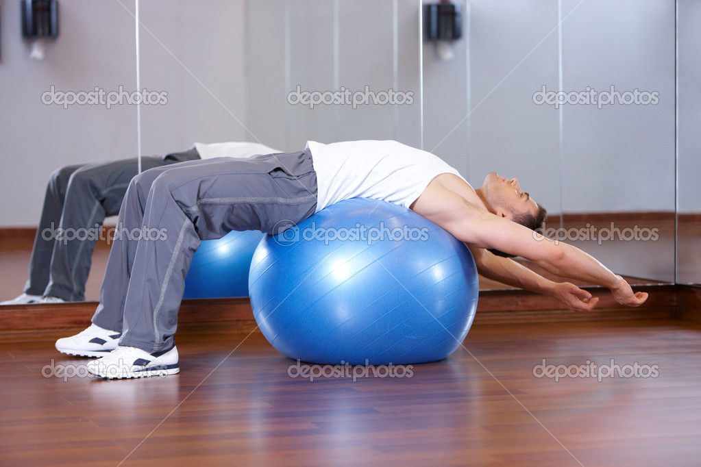Handsome man at the gym doing exercises — Stock Photo #3376083