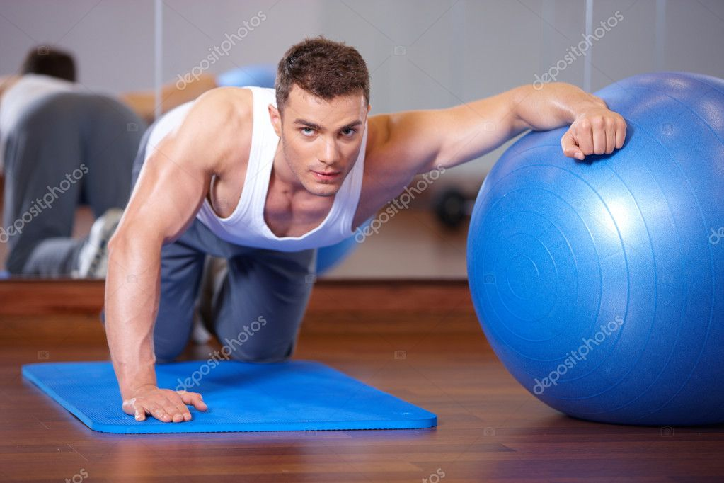 Handsome man at the gym doing exercises — Stock Photo #3376084