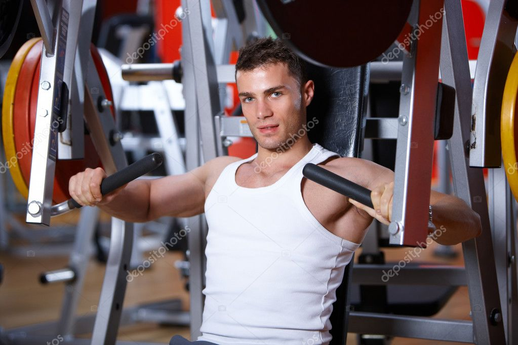 Handsome man at the gym doing exercises — Photo #3376134