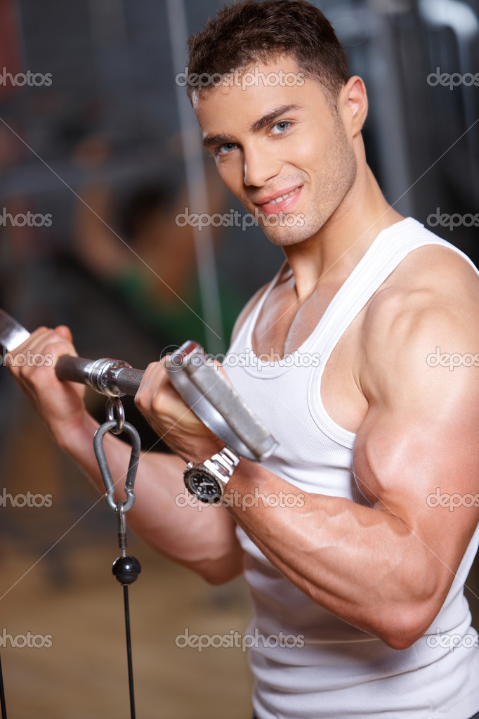 Handsome man at the gym doing exercises — Stock Photo #3376243