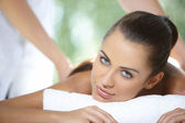 Beautiful woman is resting on spa bed — Stock Photo