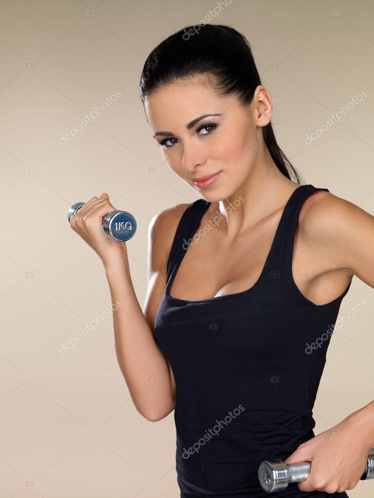 Young beautiful woman during fitness time with dumbbells — Stock Photo #3855388