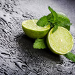 Stock Photo: Green limes with mint and water drops