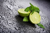 Green limes with mint and water drops — Stock Photo