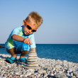 Boy building stone stack - Stock Photo
