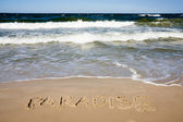 Paradise written in sandy beach — Stock Photo