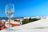 Glass of white wine against the roofs and blue sky — Stock Photo