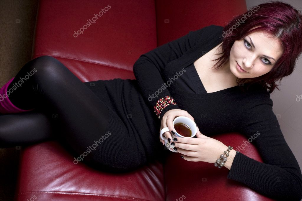 Lovely red haired woman relaxing on sofa while enjoying her morning tea while smiling at the camera. — Stock Photo #3831829