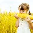 Girl eating a long loaf — Stock Photo #3184538