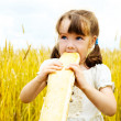 Girl eating a long loaf — Stock Photo #3184546