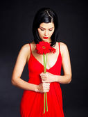 Thoughtful woman with a flower — Stock Photo