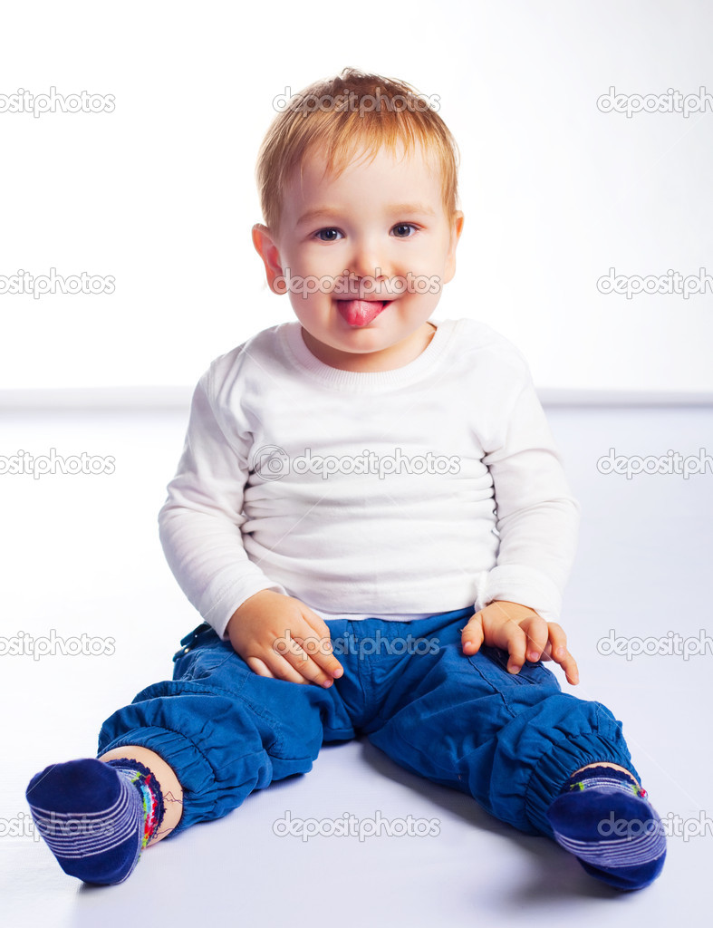 Cute happy baby sitting on the floor and showing tongue — Stock Photo #3185057