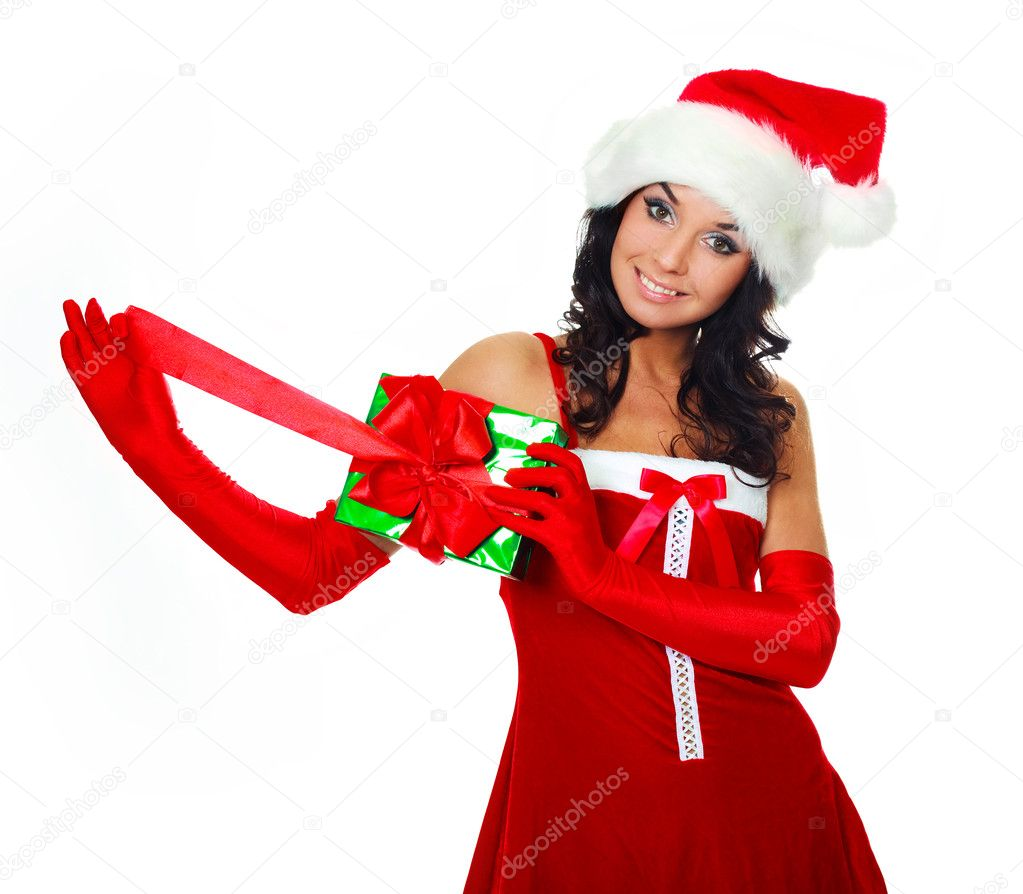 Beautiful young brunette woman wearing a Santa's hat and opening a Christmas present — Stock Photo #3187560
