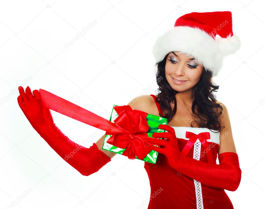 Beautiful young brunette woman wearing a Santa's hat and opening a Christmas present — Stock Photo #3187568