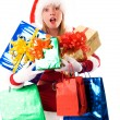 Girl dressed as Santa with presents — Stock Photo