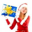 Stock Photo: Girl shaking a box with a Christmas present