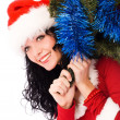 Stock Photo: Beautiful brunette woman carrying a Christmas tr