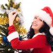Beautiful brunette woman decorating a Christmas - Stock Photo