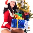 Stock Photo: Beautiful girl puts presents under the Christmas