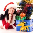 Beautiful brunette woman under the Christmas tre — Stock Photo