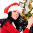 Beautiful brunette woman near the Christmas tree — Stock Photo