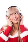 Dívka oblečený jako santa poslechu hudby — Stock fotografie