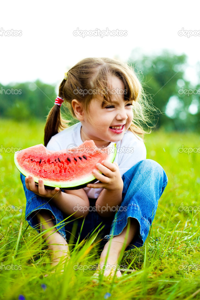 可爱的小女孩在草地上在夏日吃西瓜